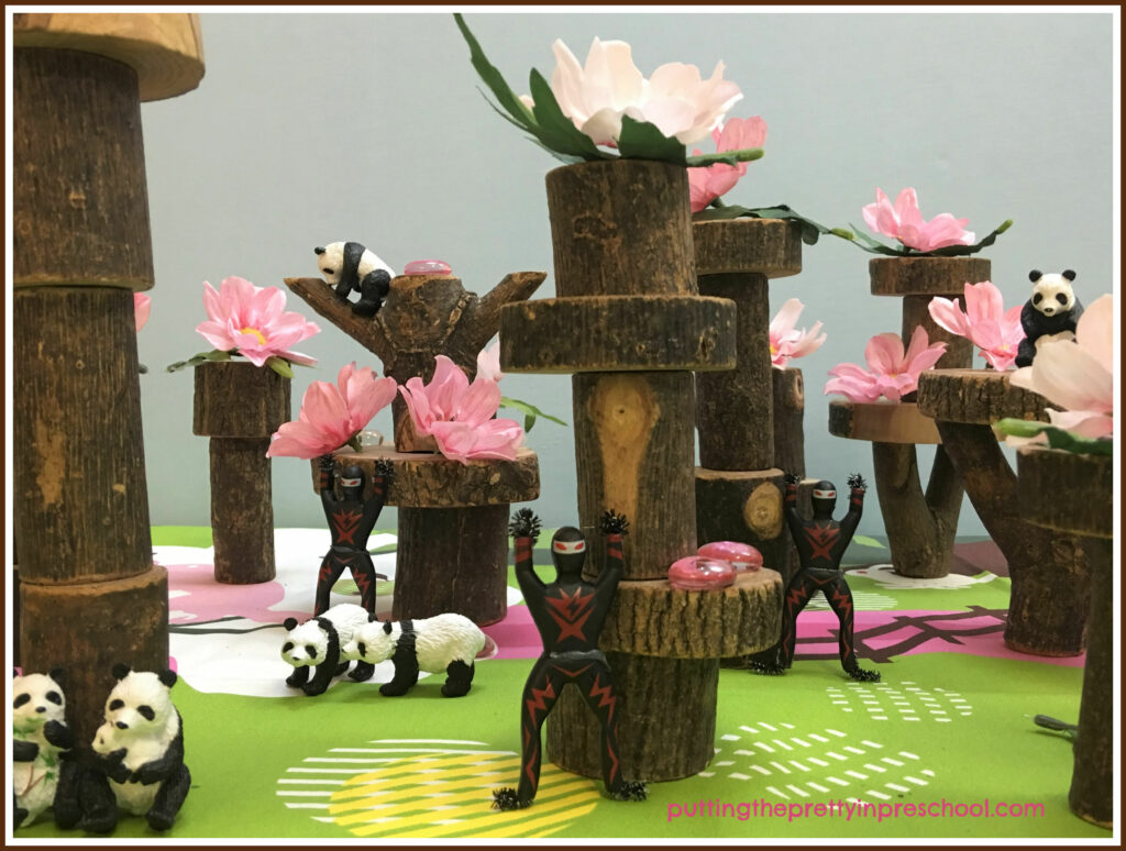 Cherry blossom tree small world with pink flowers, gems, and panda and ninja figurines.