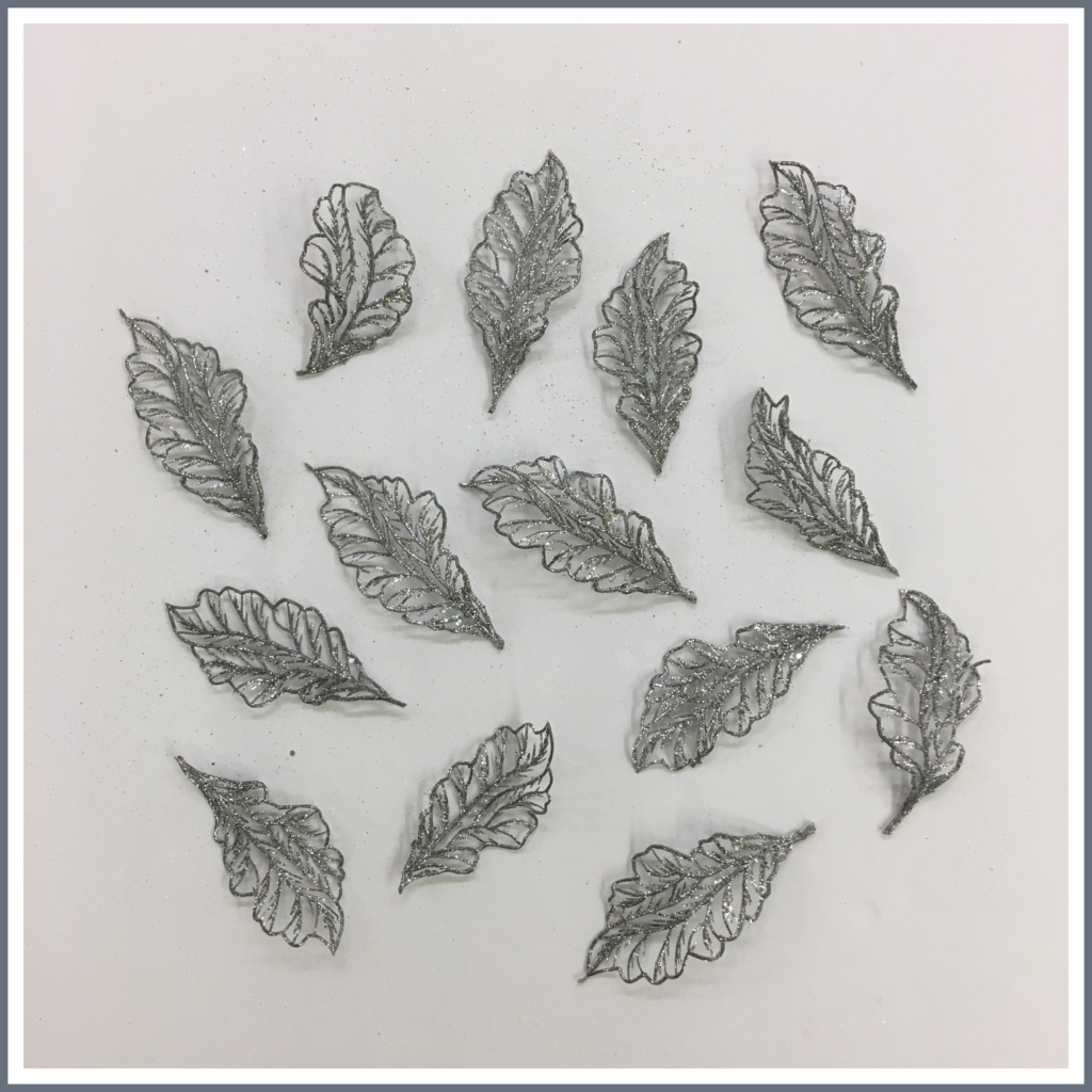 Silver metallic leaves cut from a stem.
