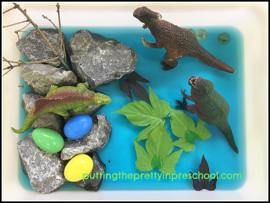 Small world scene with dinosaurs, rocks, twig, plastic eggs, marbles, blue water, and sweet potato vine leaves.