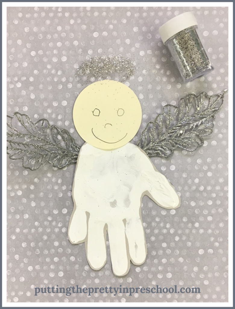 Invitation to add a silver glitter halo to a handprint angel.