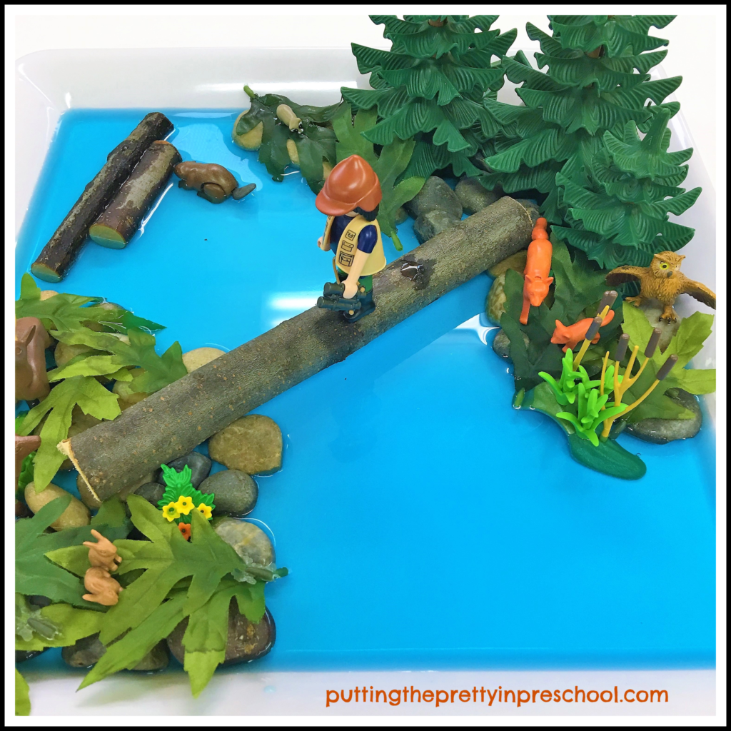 Hiking sensory tub with trees, logs, water, rocks, leaves, and forest animals.