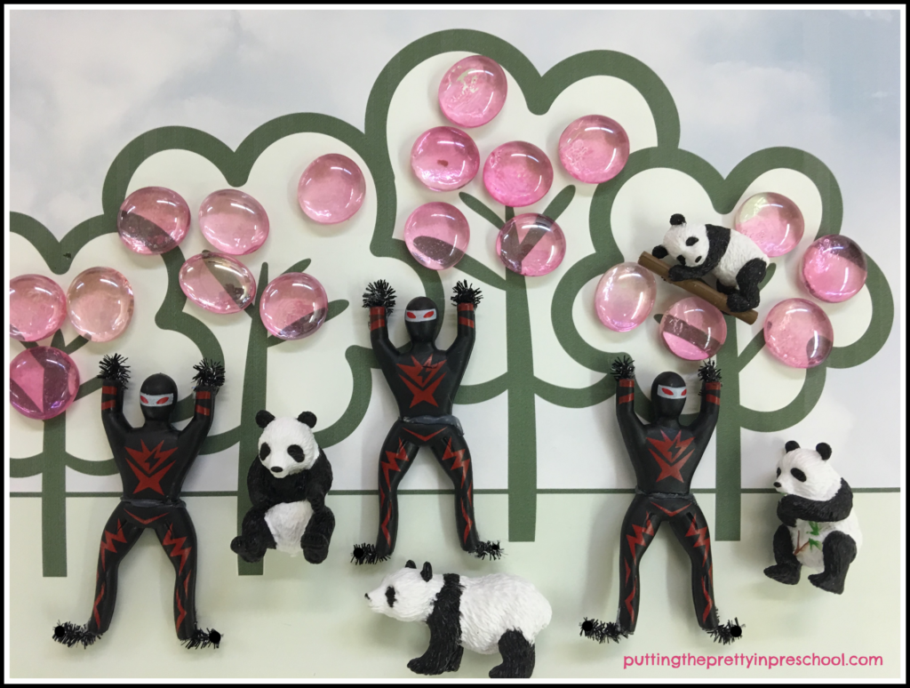 Tree placemat scene with pink gems and ninja and panda bear figurines.