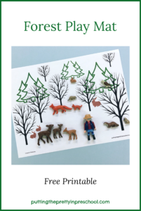 Winter Forest Play Mat with animal figures and hiker offer opportunities for imaginative play. Free printable available for download.