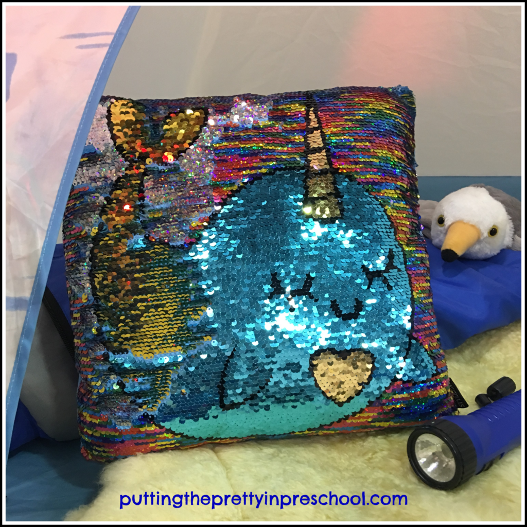 A narwhal themed sequin pillow adds a dose of glam to an igloo pretend play center.