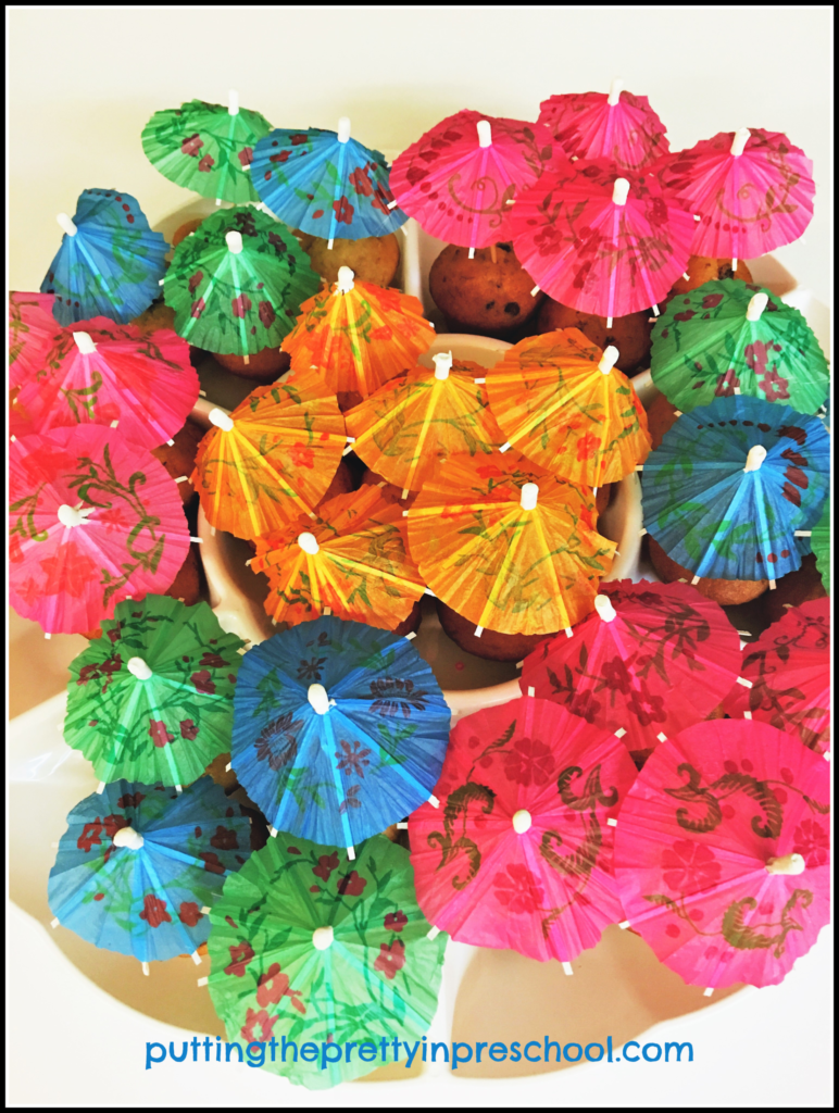 Muffins decorated with parasols for a Hawaiian party snack.