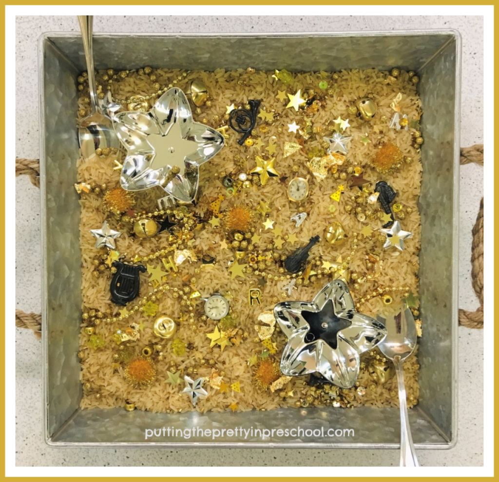 A square-shaped silver metal tray is perfect for showcasing the gold and silver pieces in this New Year's sensory play center.