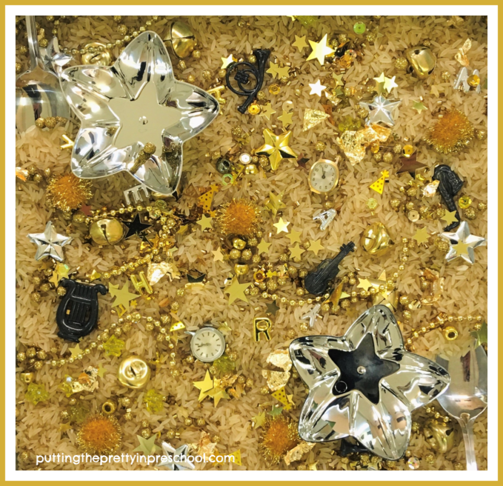 New Year's sensory tray with gold and silver pieces. Two antique watch heads are the highlights. This tray offers math, language and sensory opportunities for learning.