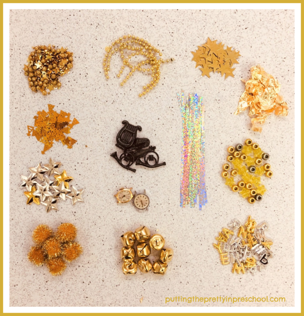 "Gold and silver supplies to use in a New Year's sensory tray. Opportunity to sort and count pieces and make sets. Invitation to spell the wish ""Happy New Year."""