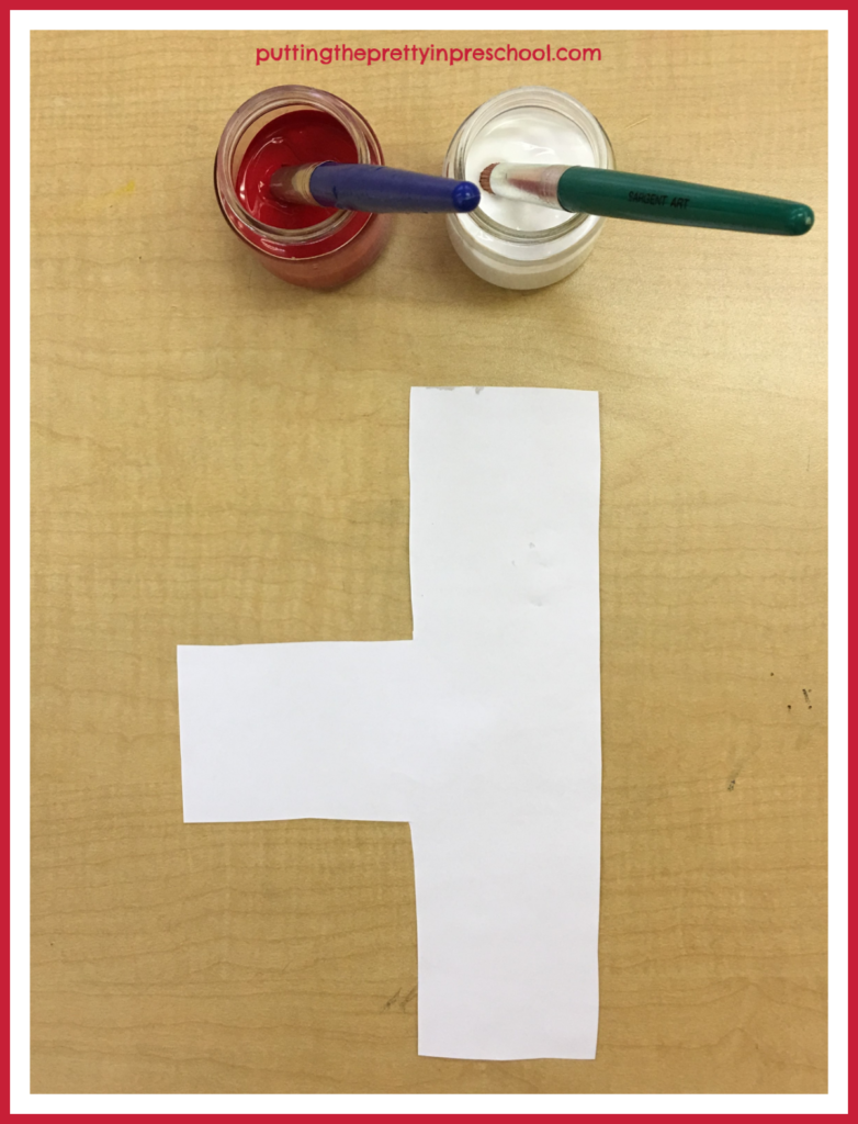 Color mixing paint activity: red and white paint set up with an unusual paper shape.