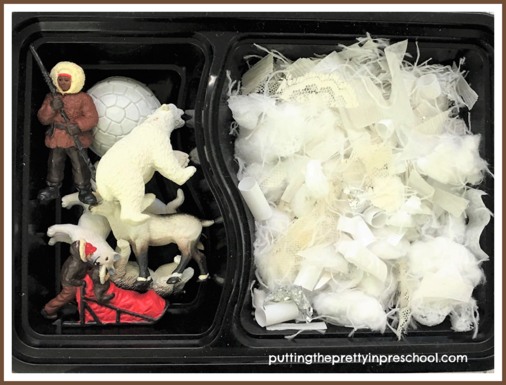 A snack tray repurposed as a small world with snipped craft supply snow and polar figurines. With a lid snapped on this play tray is transportable.