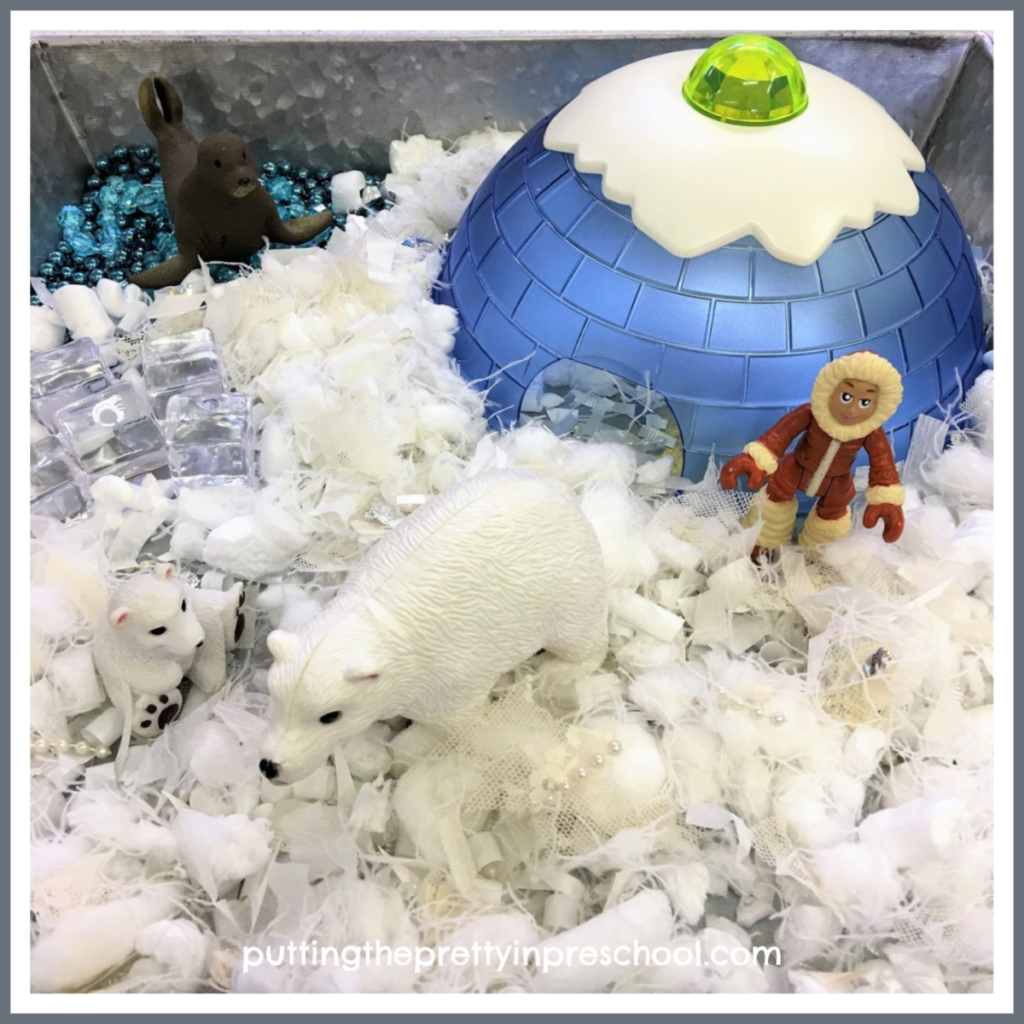 Polar small world with craft supply snipped snow, gem ice cubes, and bead garland water.