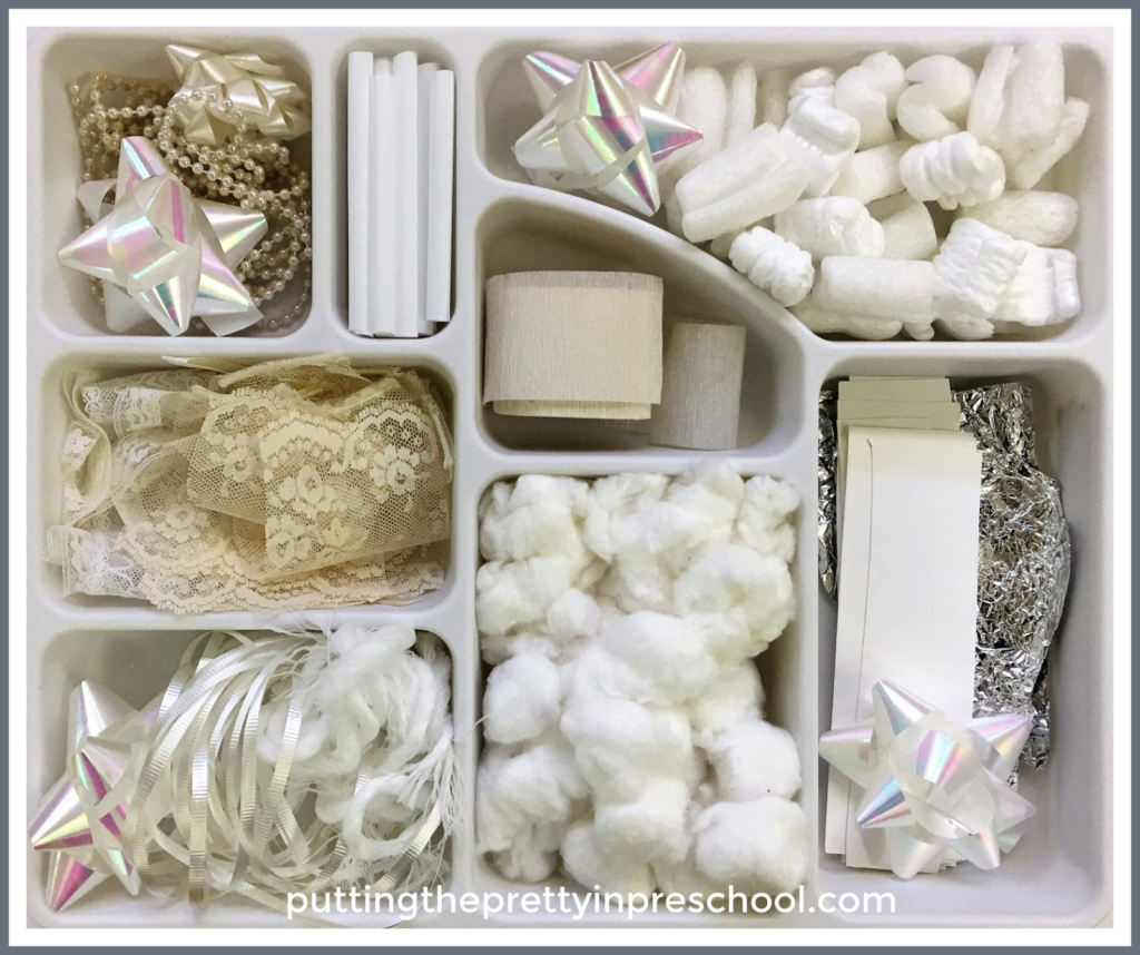 White and neutral craft supply tinker tray. Scissor skill activity to create fake snow and bits and pieces for collage and sensory activities.