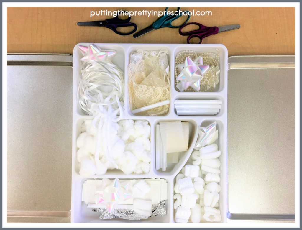White and neutral craft supply cutting tray set up. Scissor skill activity to create fake snow and bits and pieces for collage and sensory activities.