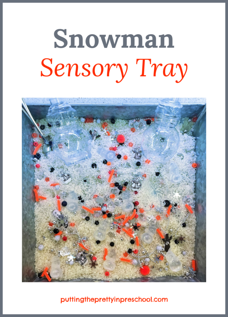 Snowman sensory tray with a rice base and loose parts. Snowman bottles, ice cubes, and buttons are the highlights of the tray.