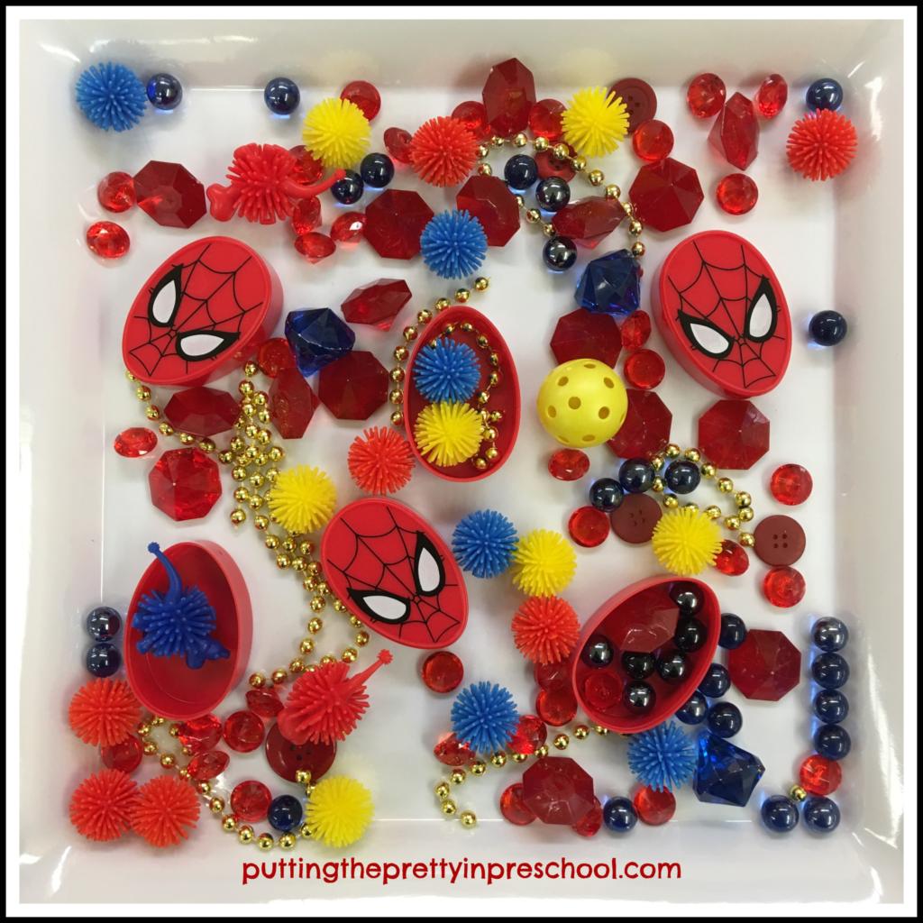 Superhero sensory tray with loose parts.