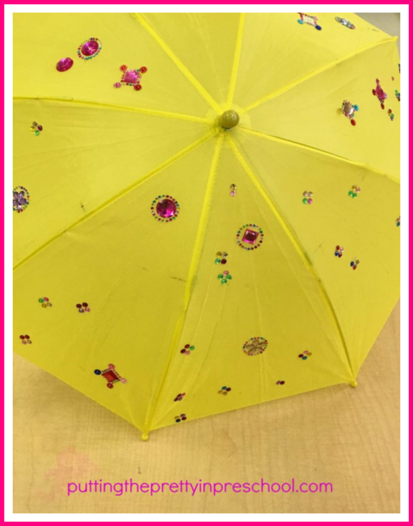 Umbrella decorating. Sticker gems and rhinestones adorn the umbrella. This project is inspired by an activity at a Chinese Valentine's Day celebration.