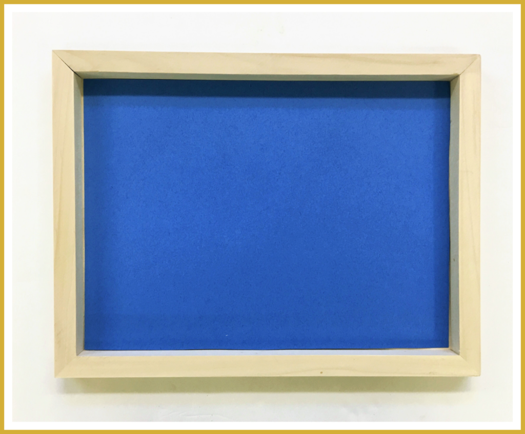 A wooden canvas paint board with a blue piece of fade-resistant paper tucked inside.