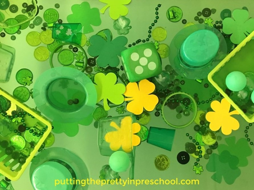 Water table filled with green and gold St. Patrick's Day-themed loose parts.