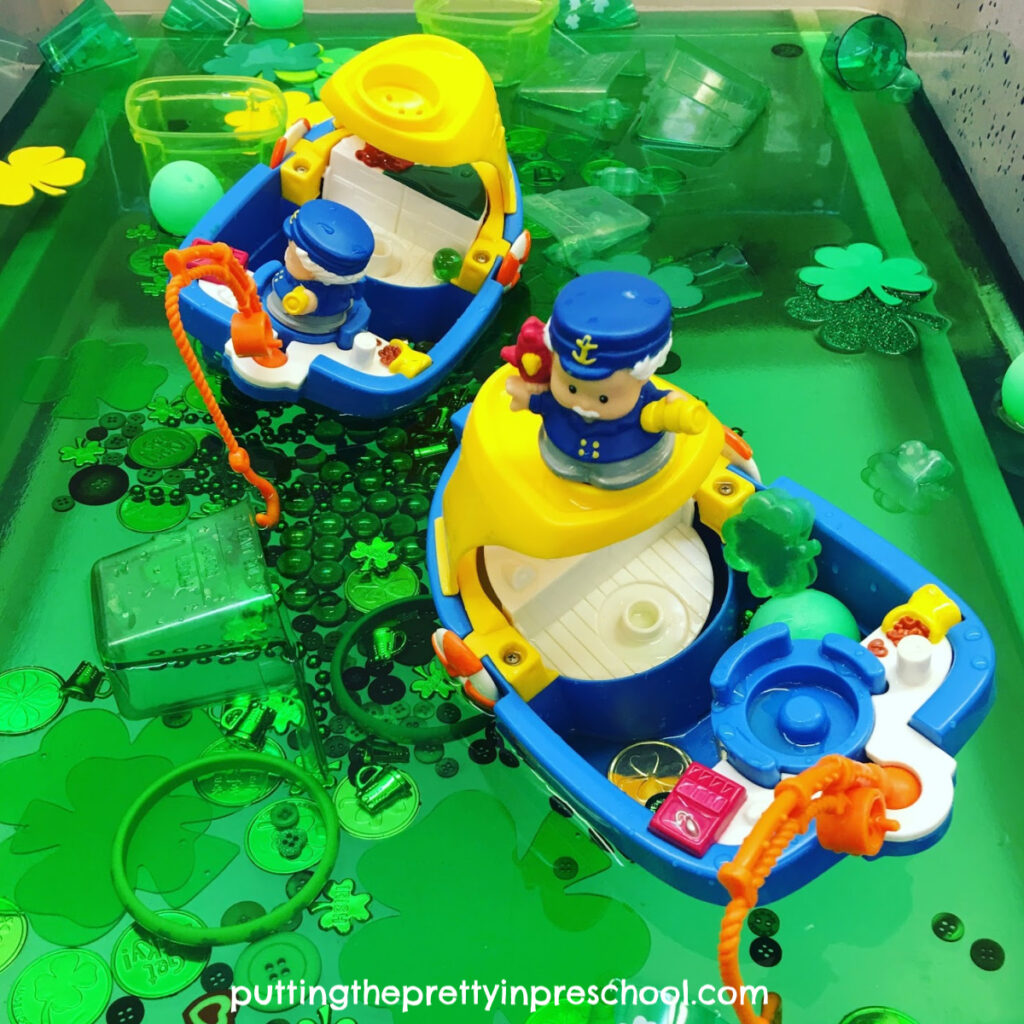 Toy boats on green water filled with St. Patrick's Day-themed loose parts offer a rich sensory play experience.