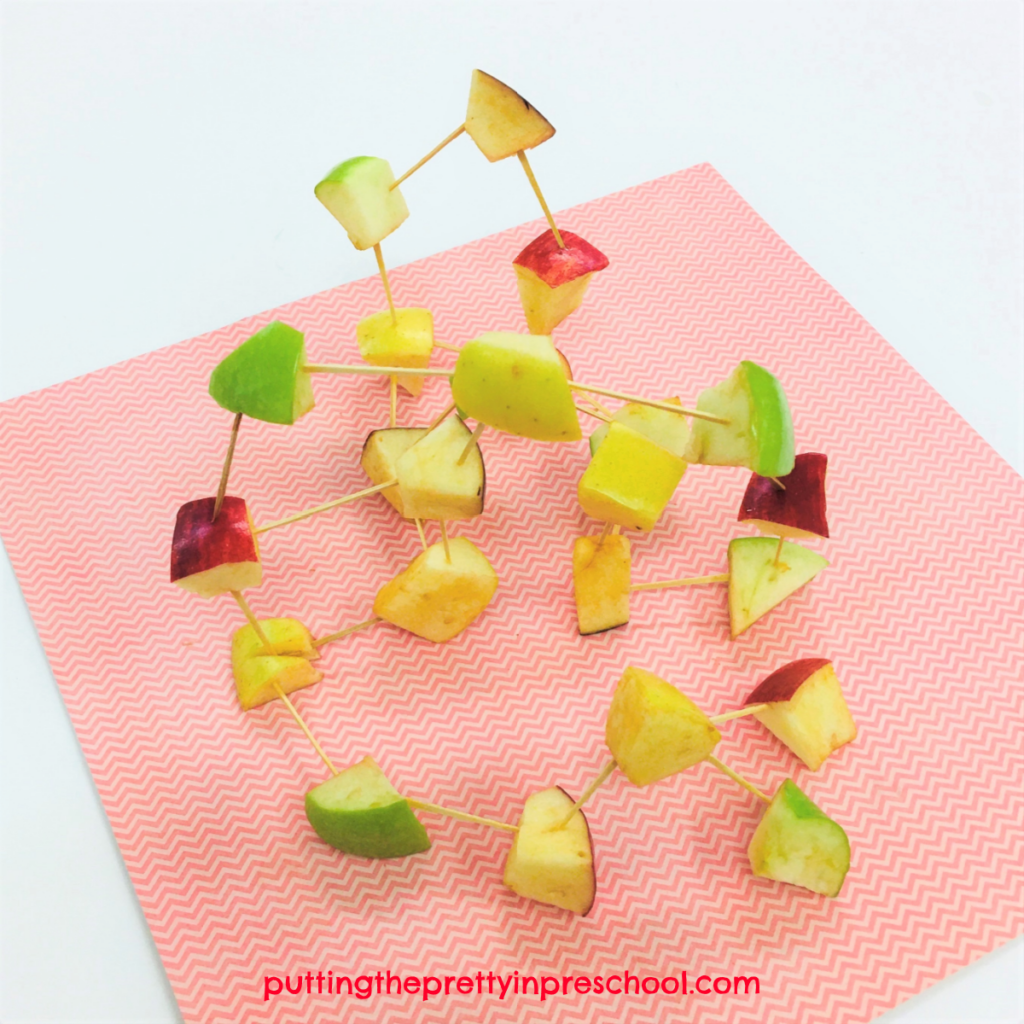 Apple chunk and toothpick sculpture. Yello, green, and red apples are used to make a colorful structure.