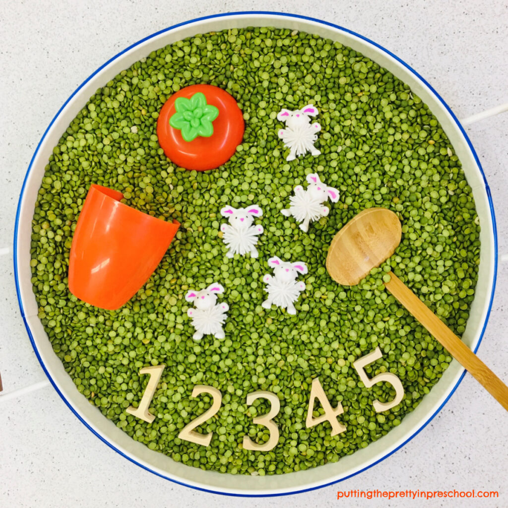 Split pea-based sensory tub with bunny woolies, numbers, ladle, and carrot cup with a lid.