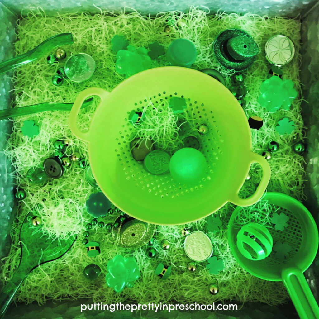 St. Patrick's Day rice noodle tray with leprechaun hats, green sieves, utensils and loose parts.