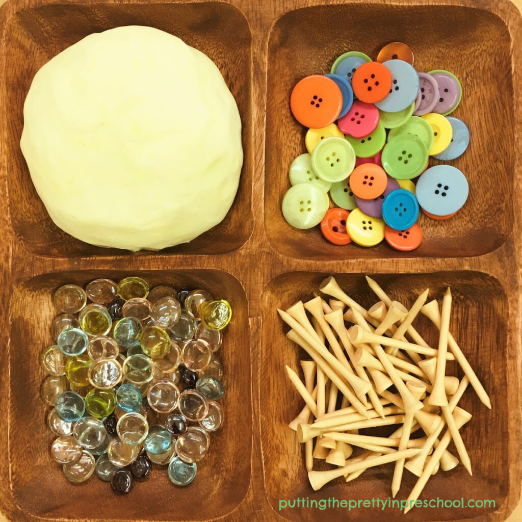 Invitation to play with coconut-scented, two-ingredient playdough and buttons, gems, and golf tees.