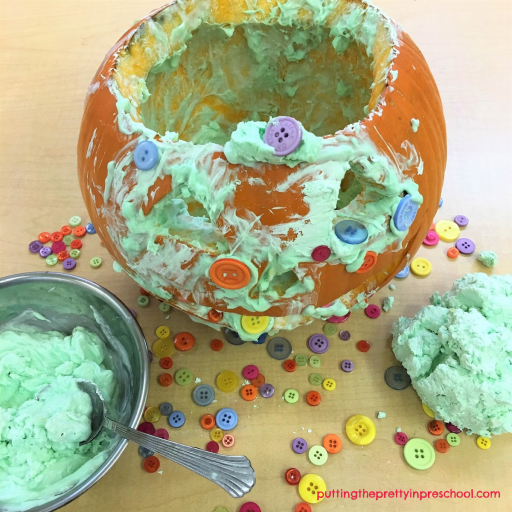 Invitation to explore scented conditioner slime and use it with buttons to decorate a pumpkin.