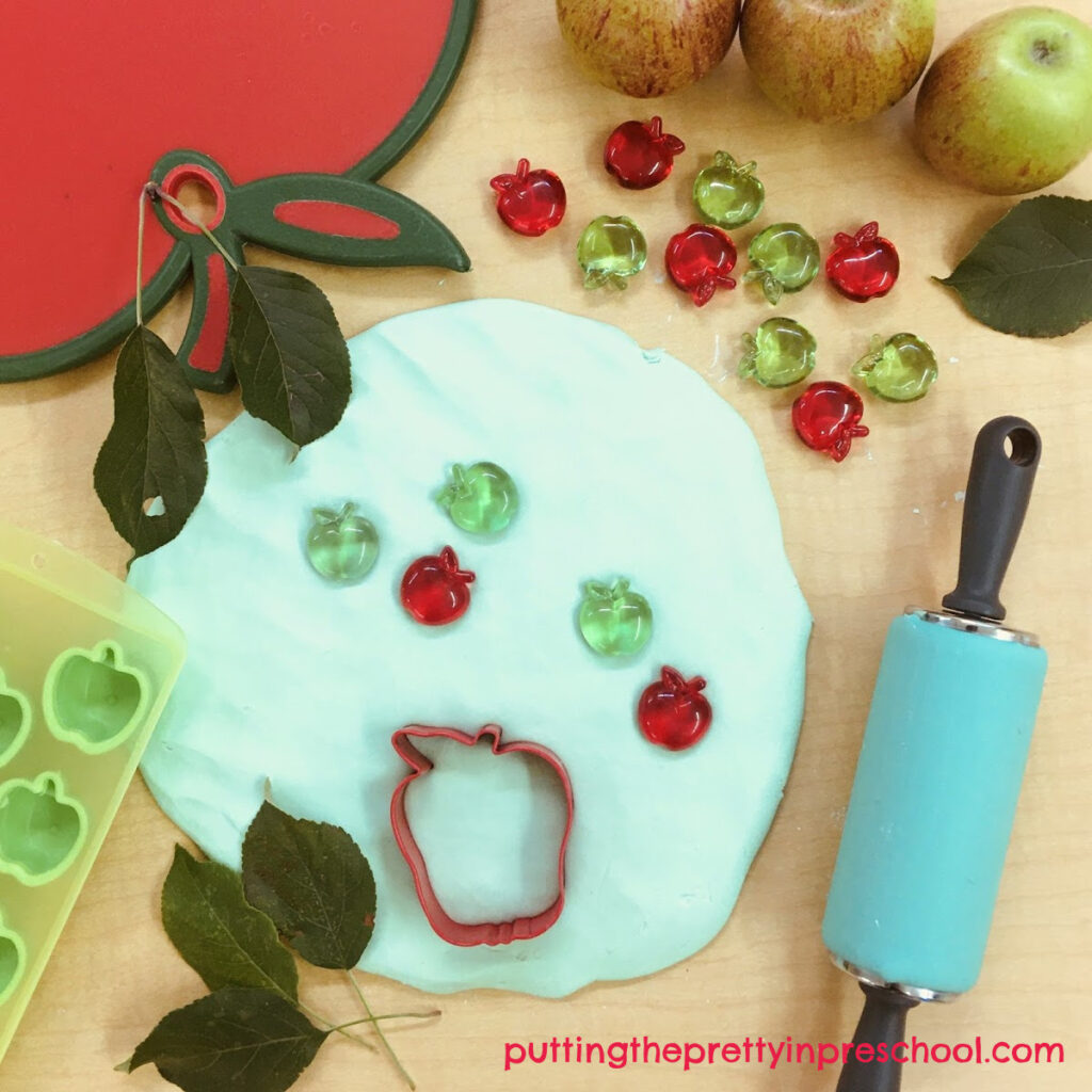 Apple themed playdough invitation with apple cutting board, ice cube tray, cookie cutters, leaves, and gems.