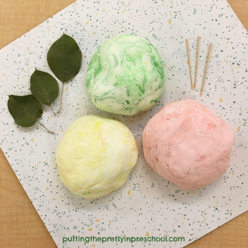 Invitation to create apples with scented, two-ingredient playdough, toothpicks, and apple leaves.