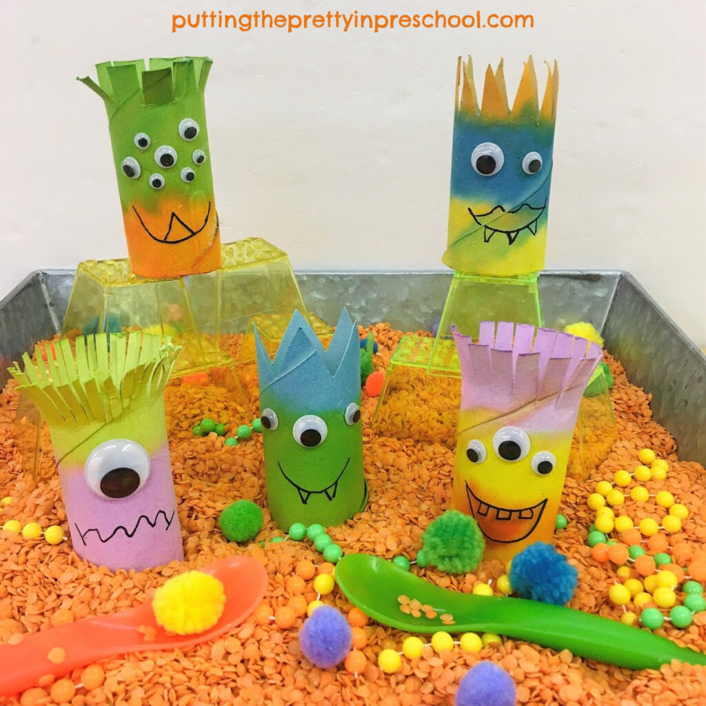 Toilet paper roll monsters in a red split lentil-based sensory bin perfect for imaginary play.