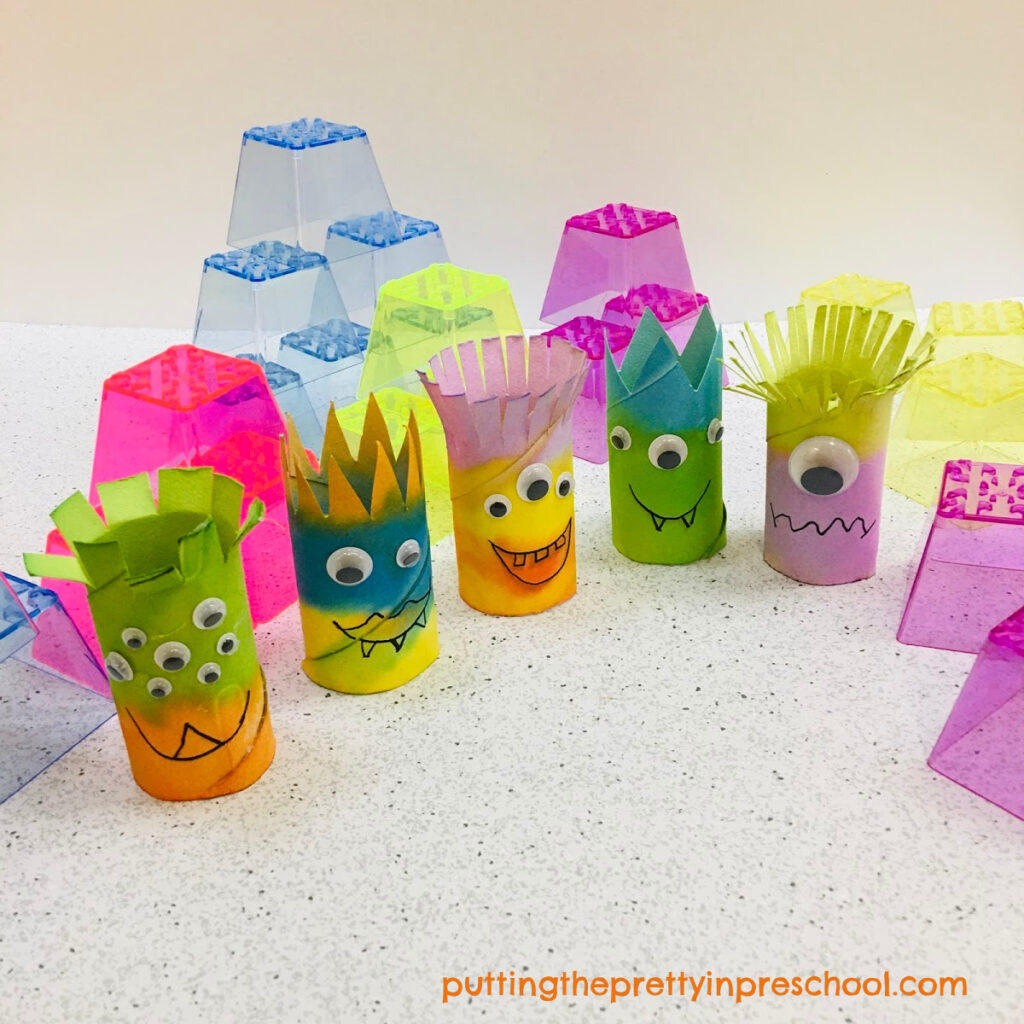 Toilet paper roll monsters with stacking blocks ready for imaginative play.