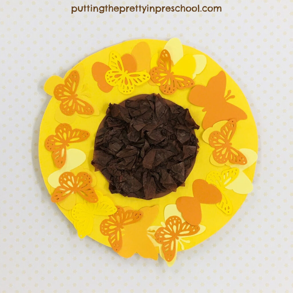 A sunflower head with a scrunched tissue center surrounded by paper butterflies.