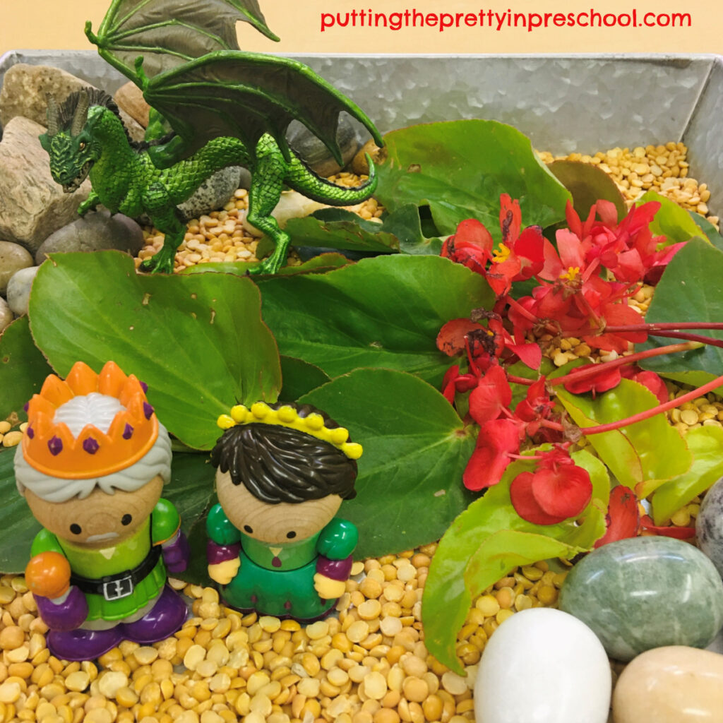 Castle-themed sensory bin with a dragon, king, princess, and dragon wing begonia leaves and flowers.