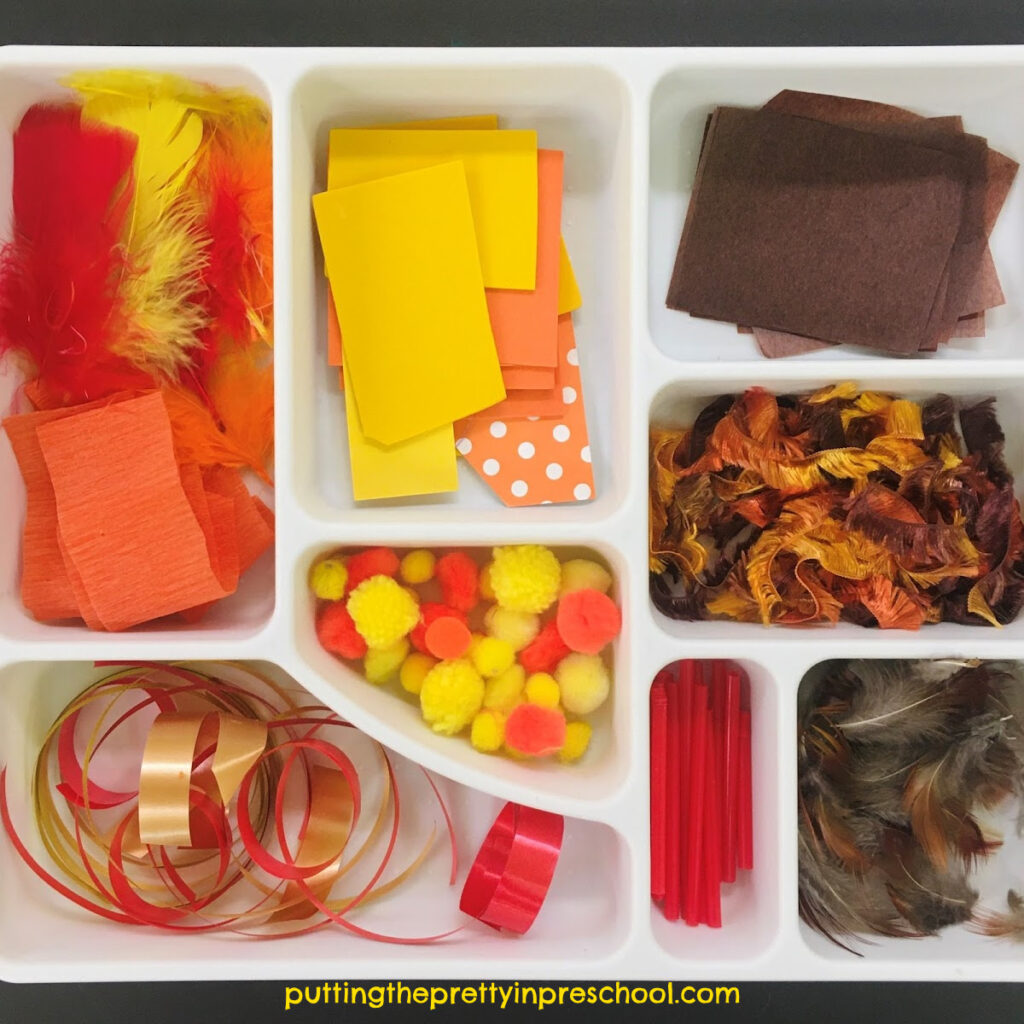 Fall scissor skills tray with red, yellow, orange, and brown craft supplies. Invitation to cut materials for collage or a sensory base.