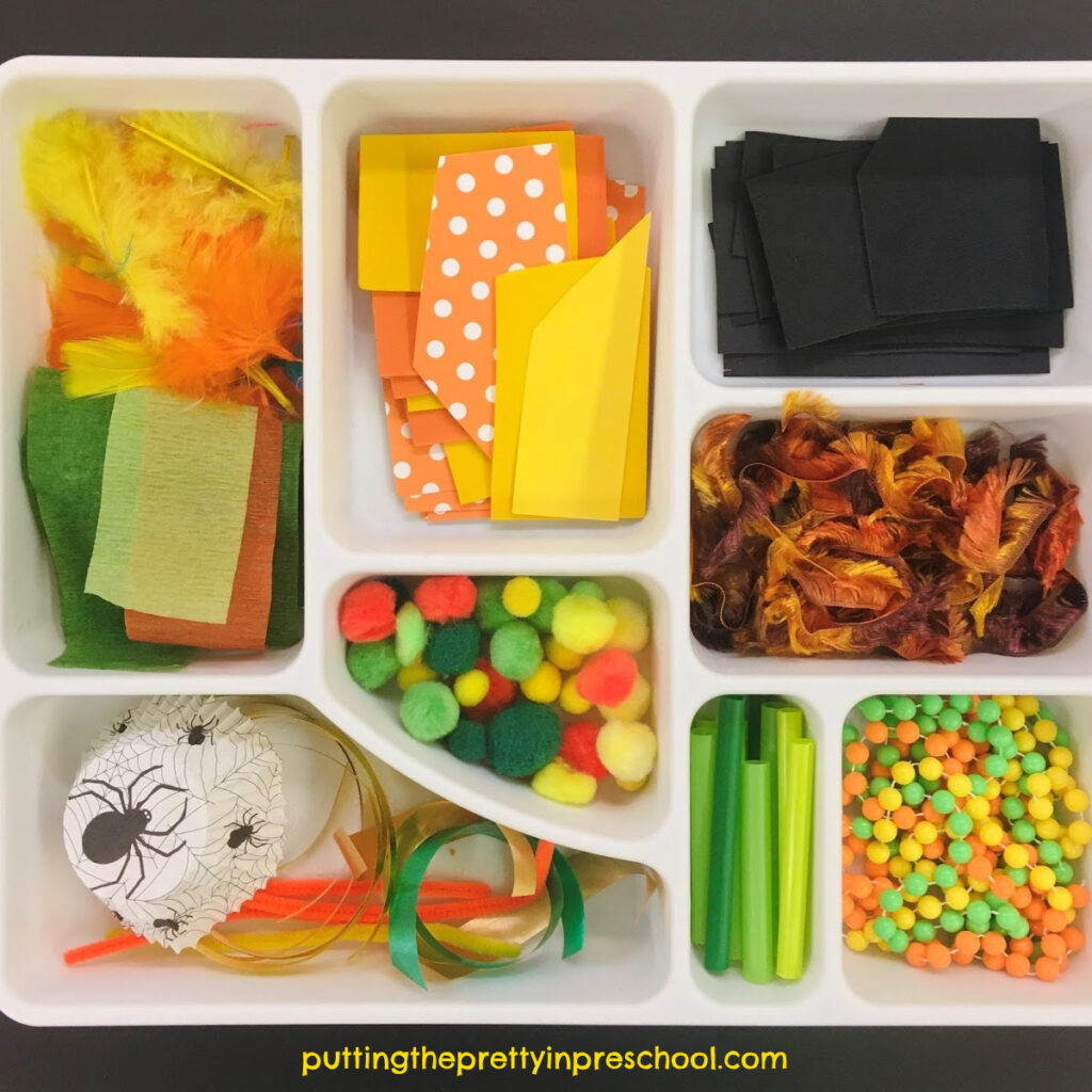 Scissor skills tray with yellow, orange, green, and black craft supplies. Invitation to cut materials for a pumpkin collage craft.