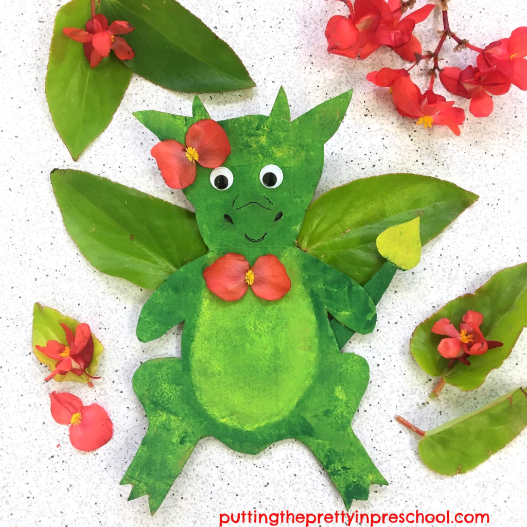 Cardboard dragon with dragon wing begonia wings and flower accents.