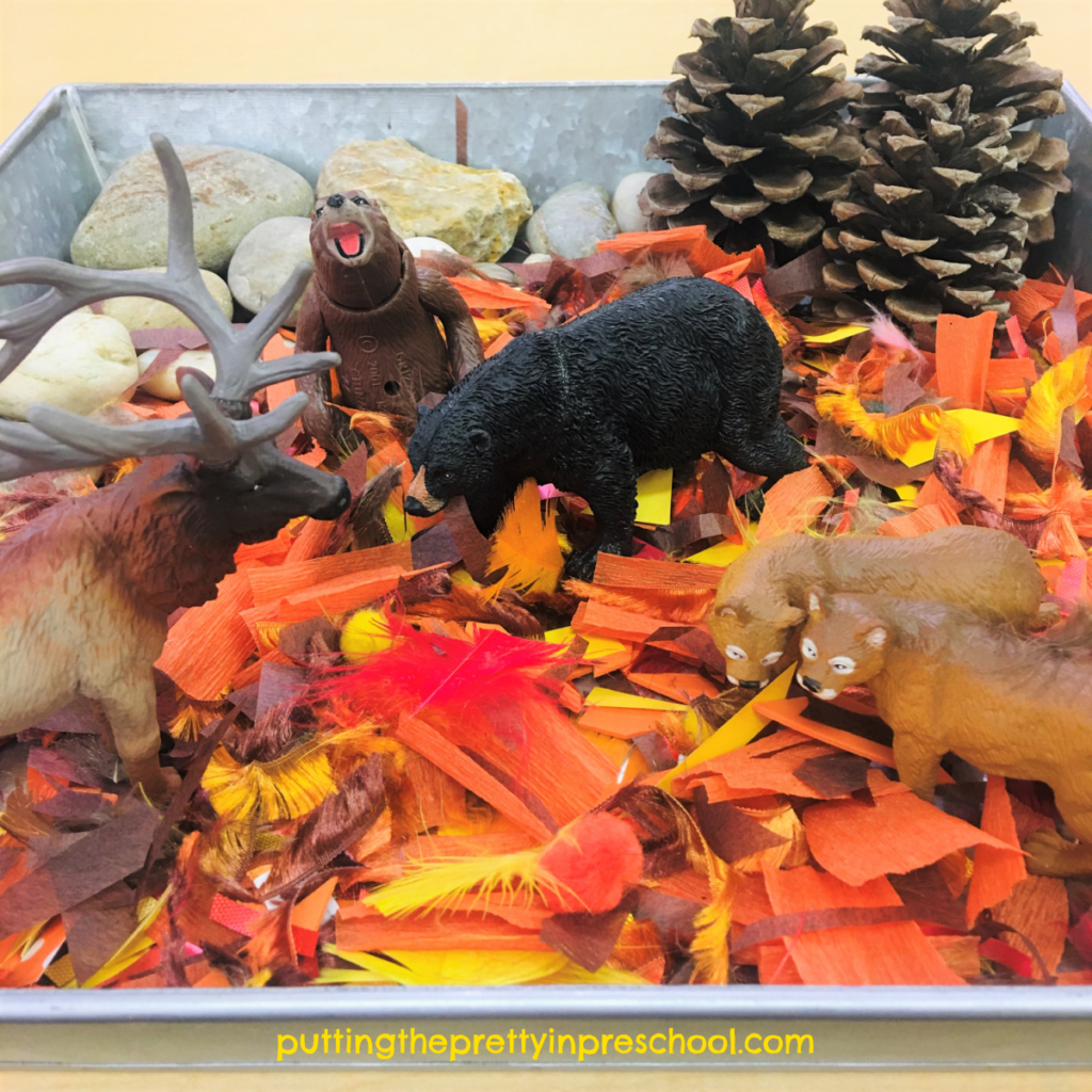 Forest sensory tray with a craft supply base. Rocks, pine cone trees, and forest animals complete the tray.