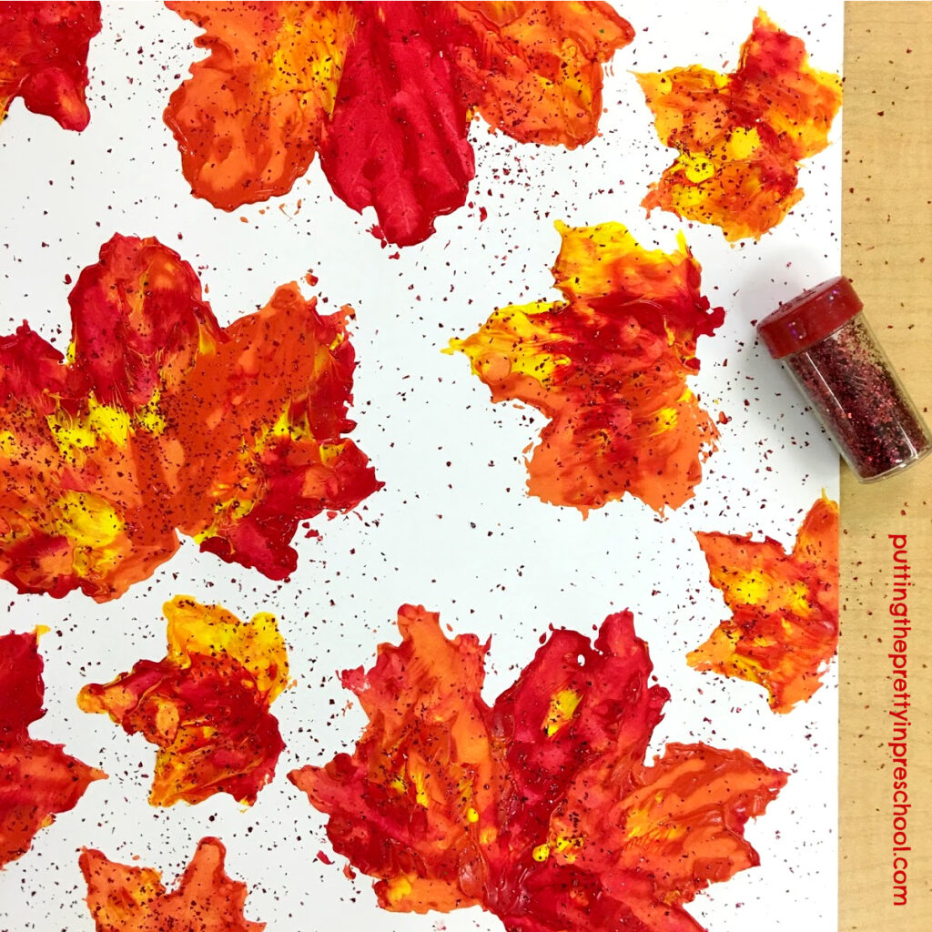 Glitter added to tempera paint maple leaf prints.