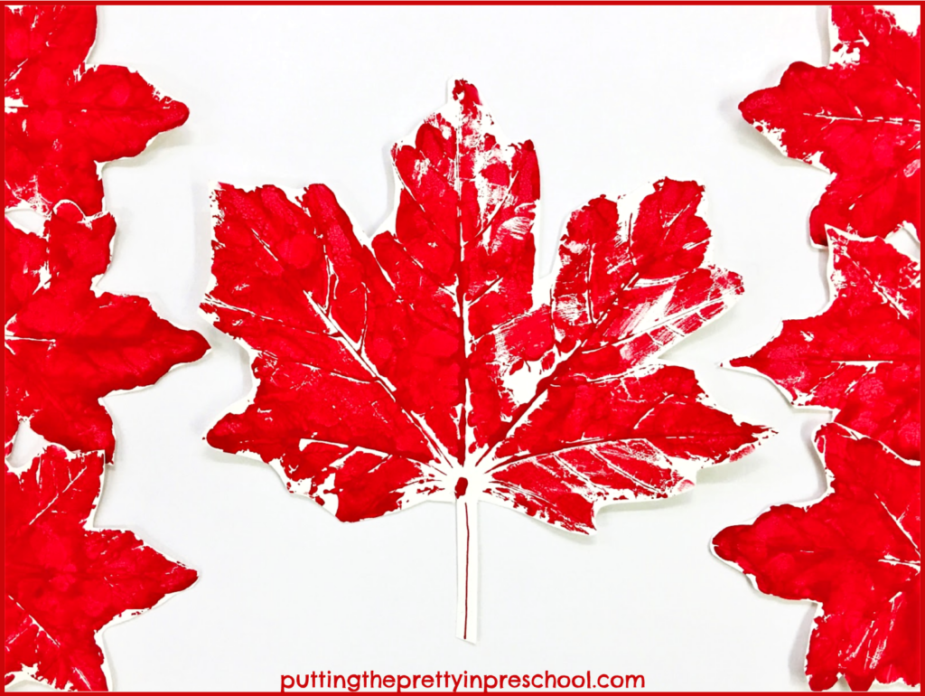 Canadian flag art made with maple leaf paint prints.