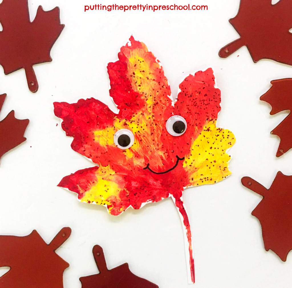 Crafted paint print maple leaf person with wiggly eyes and a permanent felt pen smile.