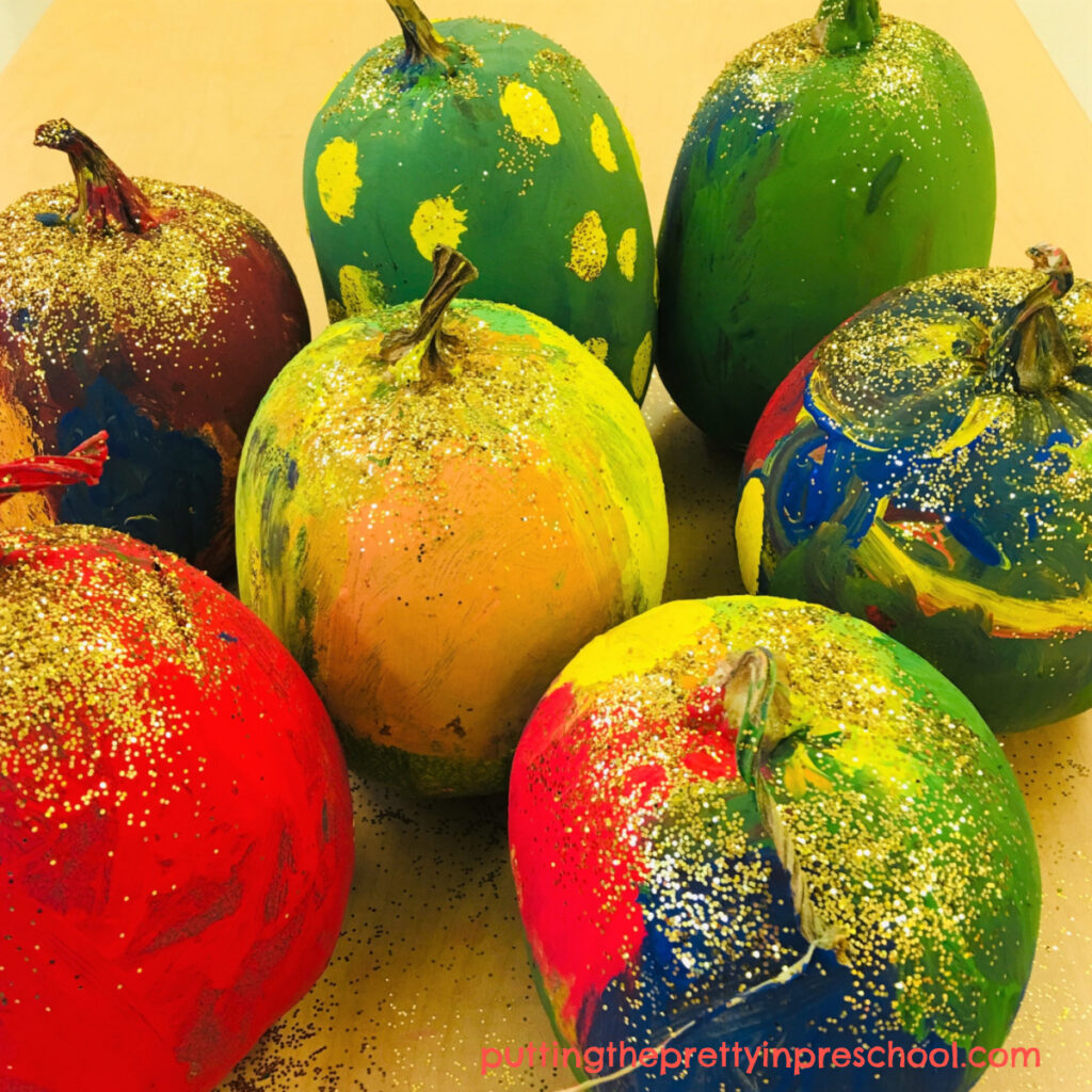 Tempera painted pumpkins sprinkled with gold glitter.