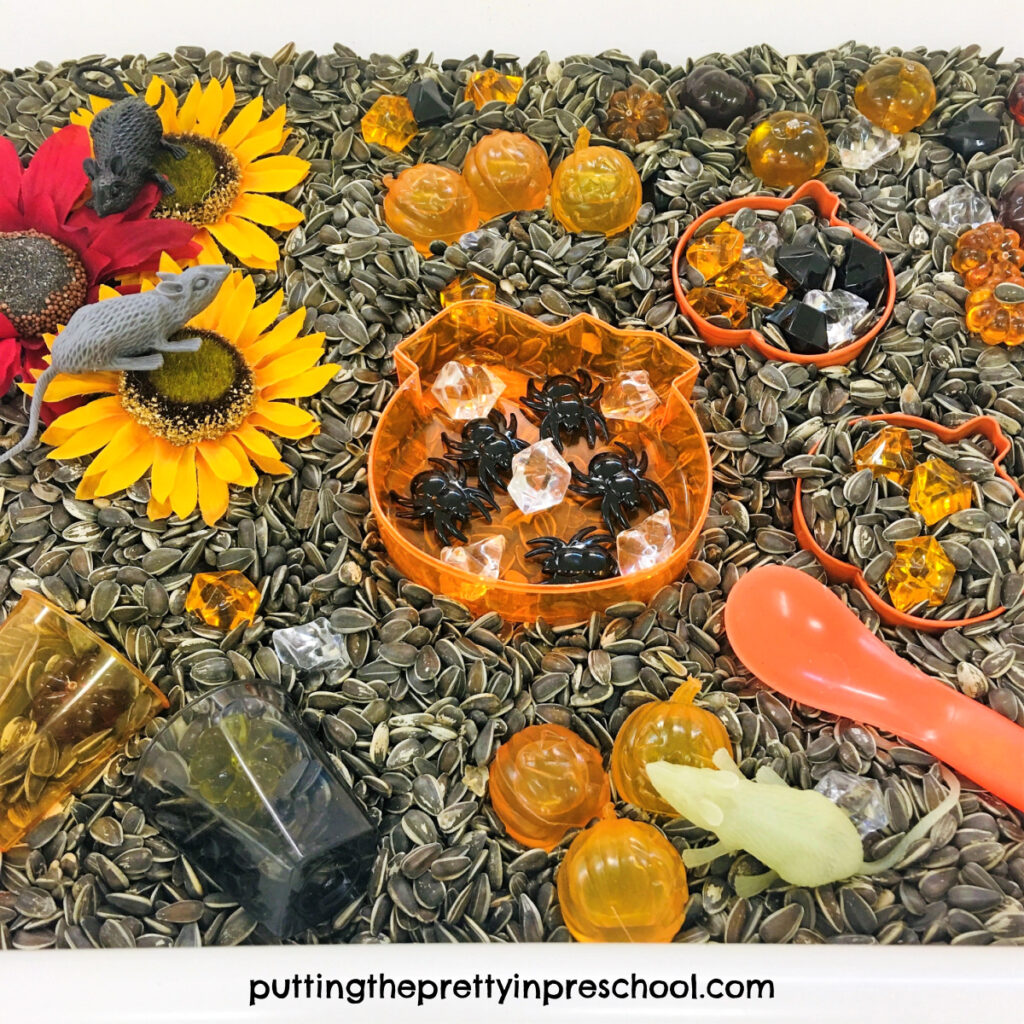 Pumpkin-themed loose parts and sunflowers shine in this sunflower seed sensory bin. Spiders and mice add fun to the tray.