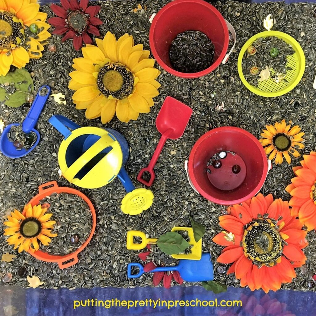 Sand toys, sunflowers, and fall-themed gems in a sunflower seed sensory bin.