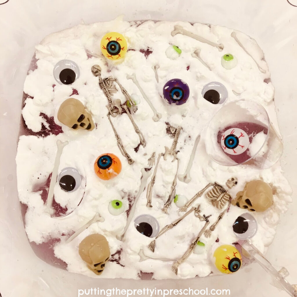 Eyeballs, wiggly eyes, skulls, bones, and skeletons float on shaving foam topped purple water in a tulip-shaped punch bowl.