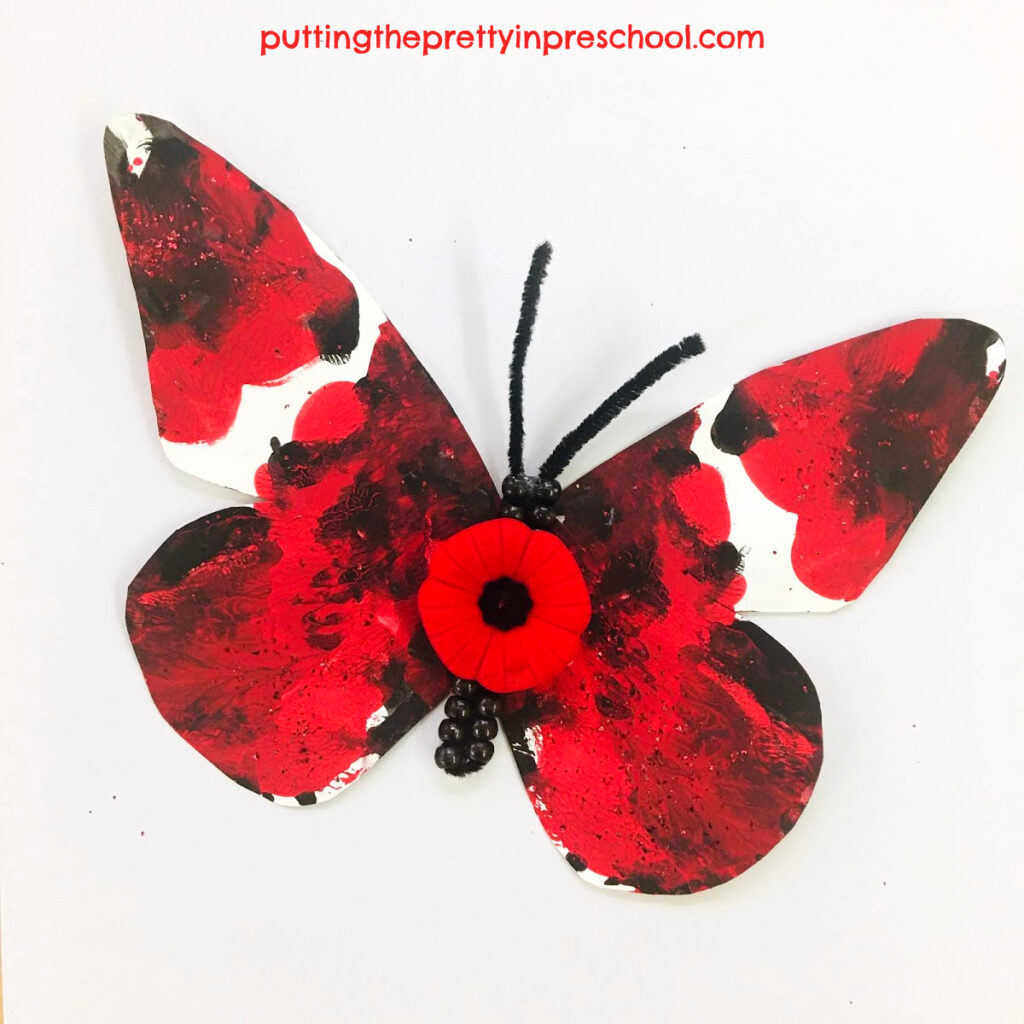 Squish painted butterfly with a poppy and beadwork for Remembrance Day.