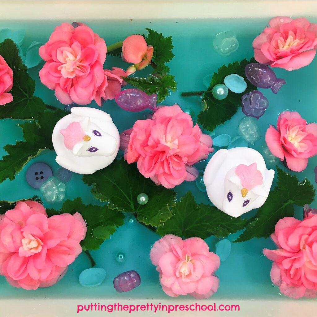 Unicorn and nonstop pink begonia sensory tub. Gem pearls, fish and flower ice cubes, shells, and buttons are part of the water tub.
