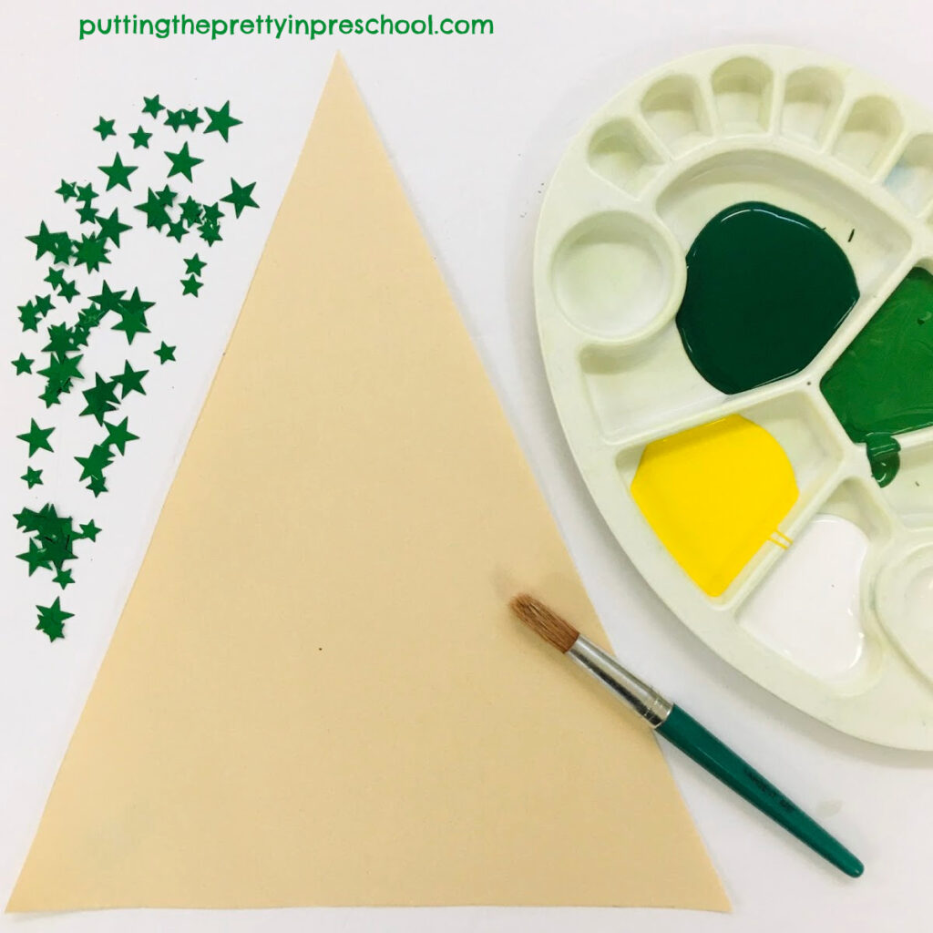 Christmas tree art set up with white, yellow, and green paint hues.