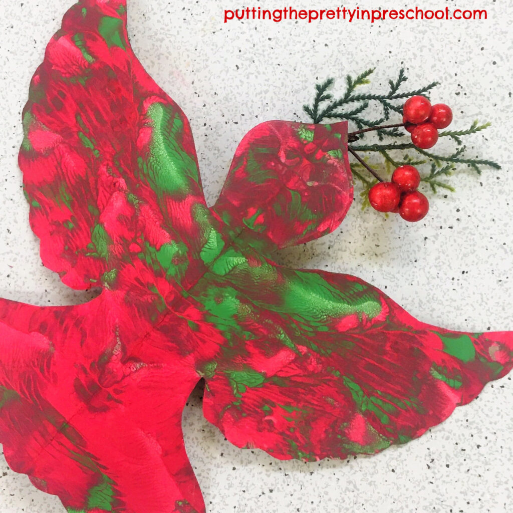 A sprig from a Christmas stem is the finishing touch for this squish painted red and green dove.