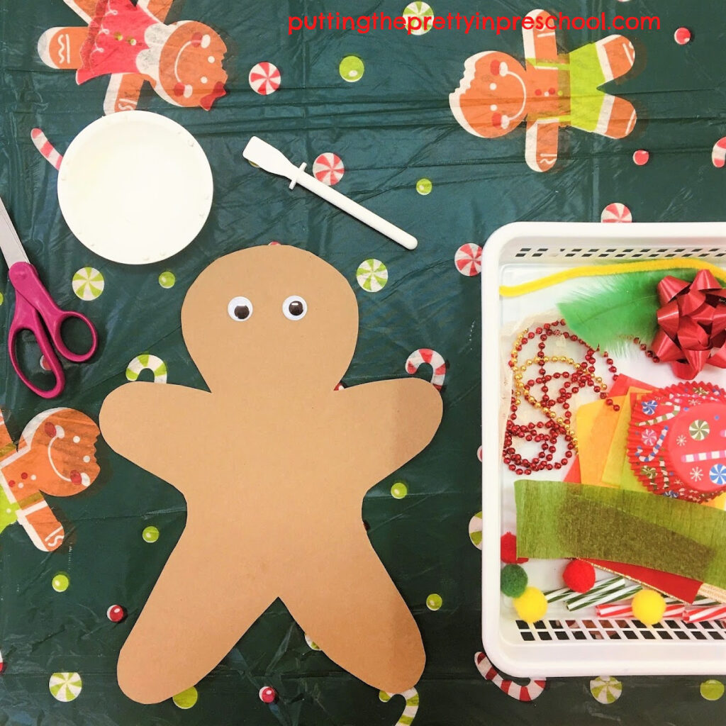 Invitation to cut and glue Christmas-themed craft supplies to decorate a kraft paper gingerbread man.